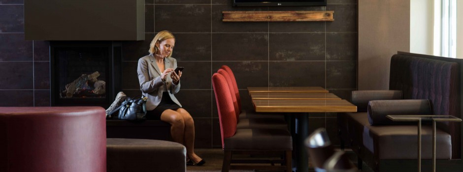 Woman Checking Email in the Lobby at Hotel Marshfield